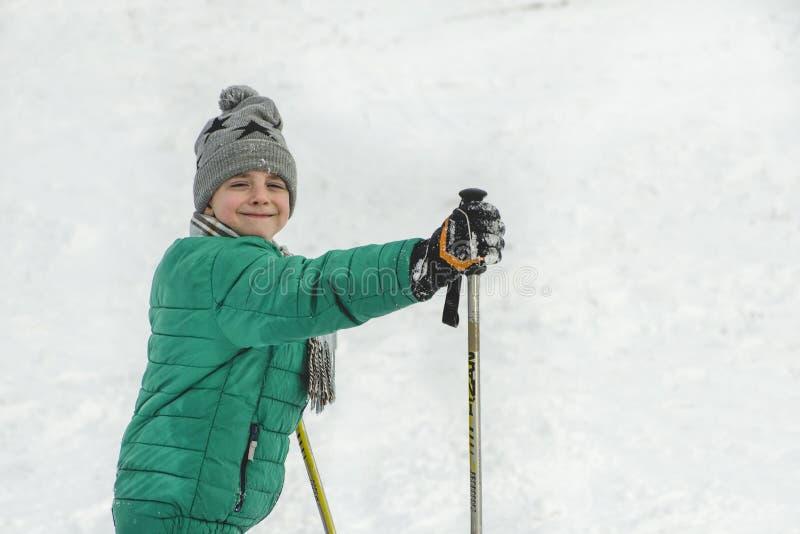 Το αγόρι σε ένα πράσινο σακάκι με τους πόλους σκι χαμογελά ο μπλε παγετός σκοτεινής μέρας κλάδων βρίσκεται χειμώνας δέντρων χιονι στοκ εικόνα με δικαίωμα ελεύθερης χρήσης
