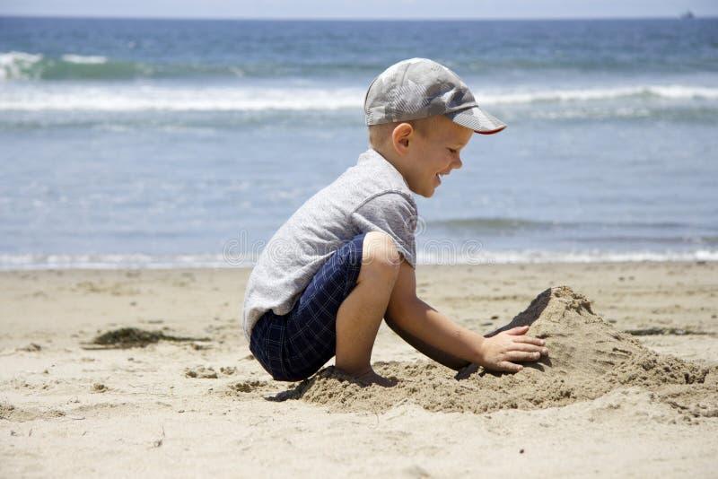 Το αγόρι στηρίζεται ένα κάστρο άμμου στην ακτή στοκ εικόνες