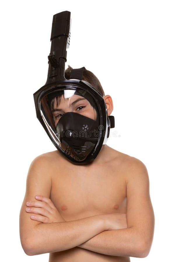 Το αγόρι στη μάσκα πλήρης-προσώπου για την κατάδυση, όπλα διέσχισε στο στήθος, χαμόγελα στη κάμερα, σε ένα άσπρο υπόβαθρο στοκ εικόνα