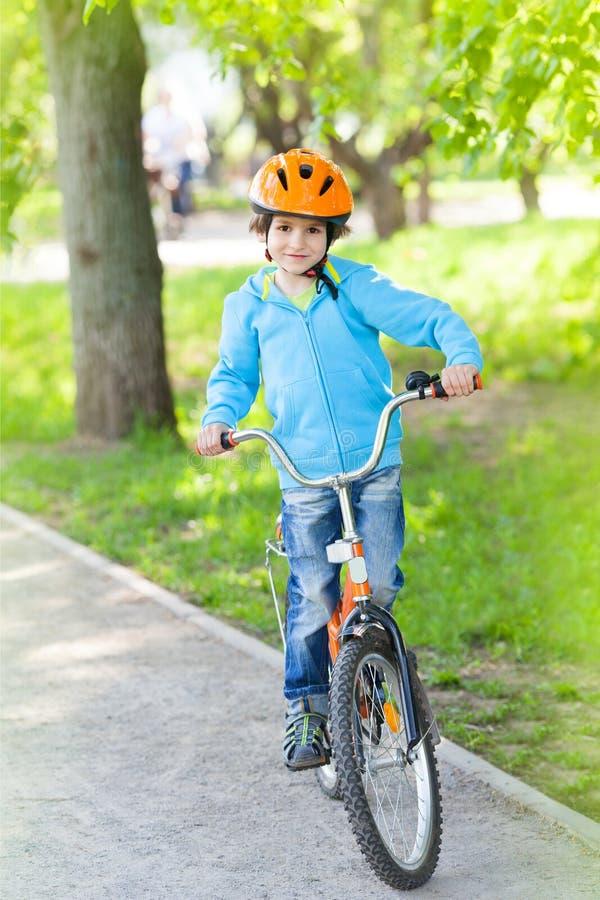 Το αγόρι στη μπλε ζακέτα οδηγά το ποδήλατο στοκ εικόνες με δικαίωμα ελεύθερης χρήσης