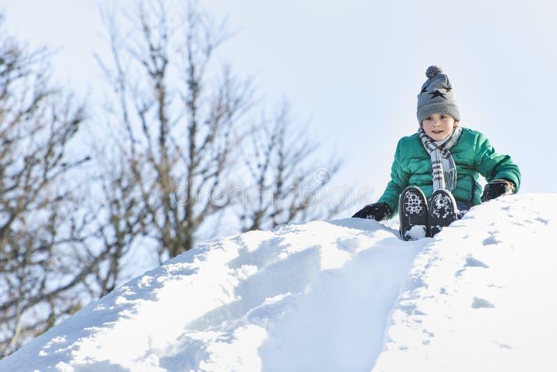 Το αγόρι στο καπέλο, το μαντίλι και το πράσινο σακάκι γλιστρά κάτω από μια φωτογραφική διαφάνεια χιονιού στην πλάτη ο μπλε παγετό στοκ εικόνες