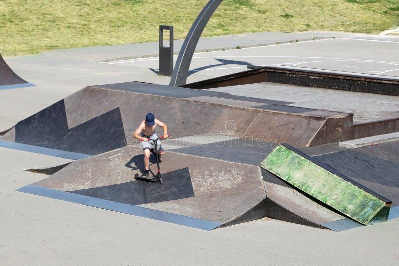 Το αγόρι στο μηχανικό δίκυκλο εκτελεί τις ακροβατικές επιδείξεις στο χώρο για τον ακραίο αθλητισμό στοκ εικόνες με δικαίωμα ελεύθερης χρήσης