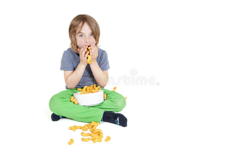 Το αγόρι τρώει τα τσιπ φυστικιών στοκ φωτογραφία