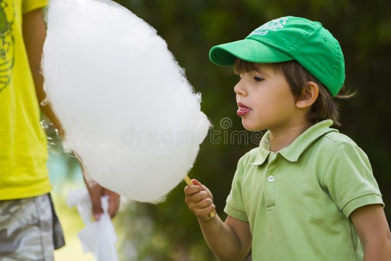 Το αγόρι τρώει το μαλλί της γριάς στοκ φωτογραφία