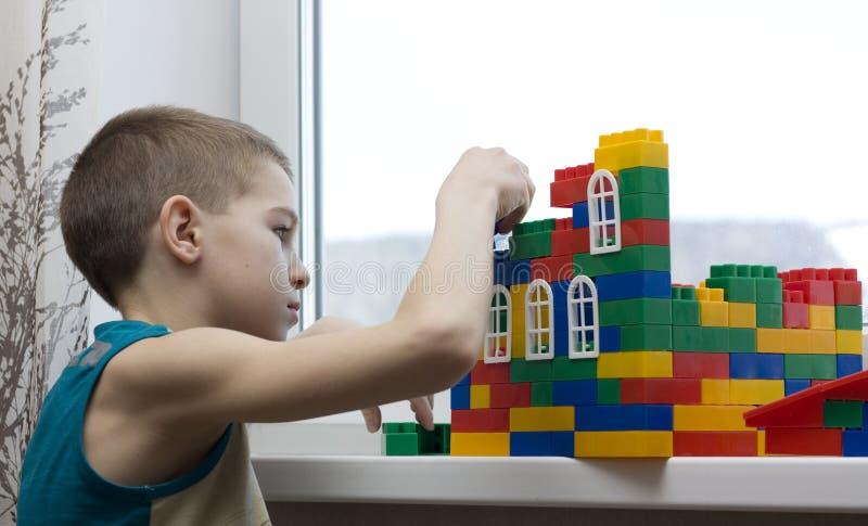 Download το αγόρι χτίζει το σπίτι στοκ εικόνα. εικόνα από συγκεντρωμένος - 13185059