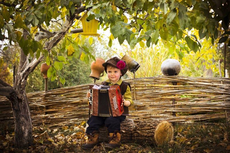 Το αγόρι χώρας με ένα ακκορντέον τραγουδά το τραγούδι στοκ εικόνες