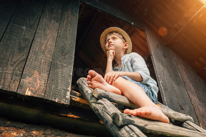 Το αγόρι Dreming κάθεται στον ηγέτη σιταποθηκών στοκ εικόνα