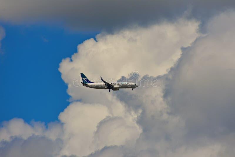Το αεροπλάνο από τις αερογραμμές Westjet, προσγειώνεται στον αερολιμένα του Ορλάντο στον όμορφο ουρανό backround στοκ φωτογραφία με δικαίωμα ελεύθερης χρήσης