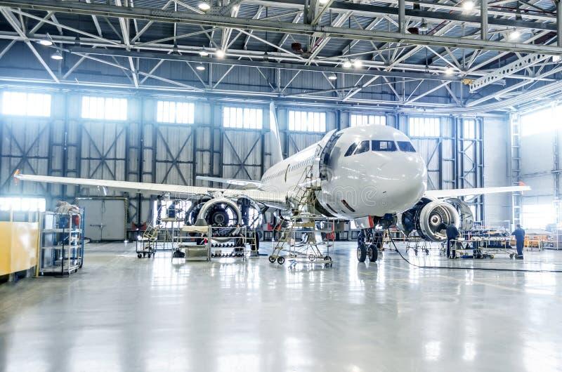 Το αεροπλάνο επιβατών στη συντήρηση της μηχανής και η άτρακτος ελέγχουν την επισκευή στο υπόστεγο αερολιμένων στοκ φωτογραφίες