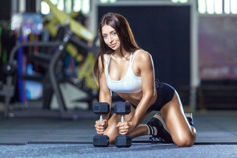 Το αθλητικό θηλυκό κάθεται σε ένα πάτωμα sportswear σε μια λέσχη γυμναστικής κοντά στους αλτήρες στοκ φωτογραφίες