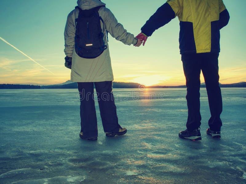 Το αθλητικό κορίτσι κρατά το χέρι αγοριών Άνθρωποι στα χειμερινά ενδύματα που τρέχουν μακριά στον ορίζοντα της παγωμένης θάλασσας στοκ φωτογραφία με δικαίωμα ελεύθερης χρήσης