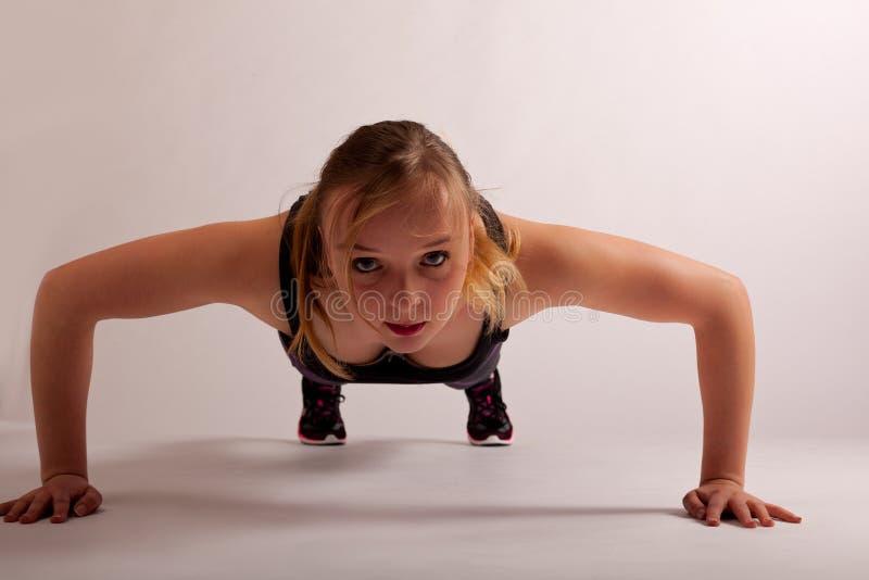 Το αθλητικό κορίτσι θέτει ώθηση-επάνω στοκ φωτογραφία