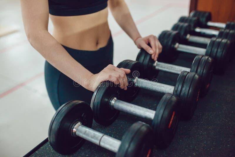 Το αθλητικό κορίτσι προετοιμάζεται για την άσκηση με τους αλτήρες στοκ φωτογραφία
