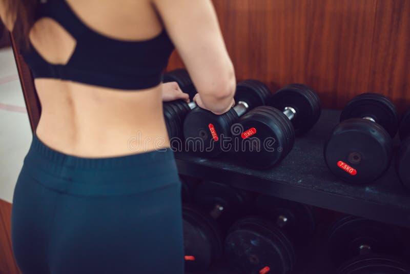 Το αθλητικό κορίτσι προετοιμάζεται για την άσκηση με τους αλτήρες στοκ φωτογραφίες
