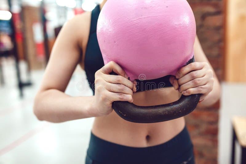Το αθλητικό κορίτσι προετοιμάζεται να ασκήσει με το kettlebel στοκ εικόνα