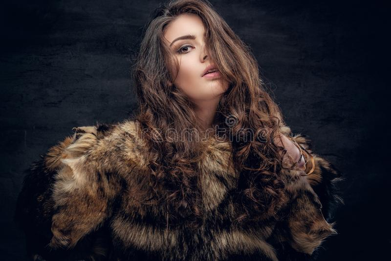 Το αισθησιακό θηλυκό brunette έντυσε σε ένα παλτό γουνών στοκ φωτογραφίες
