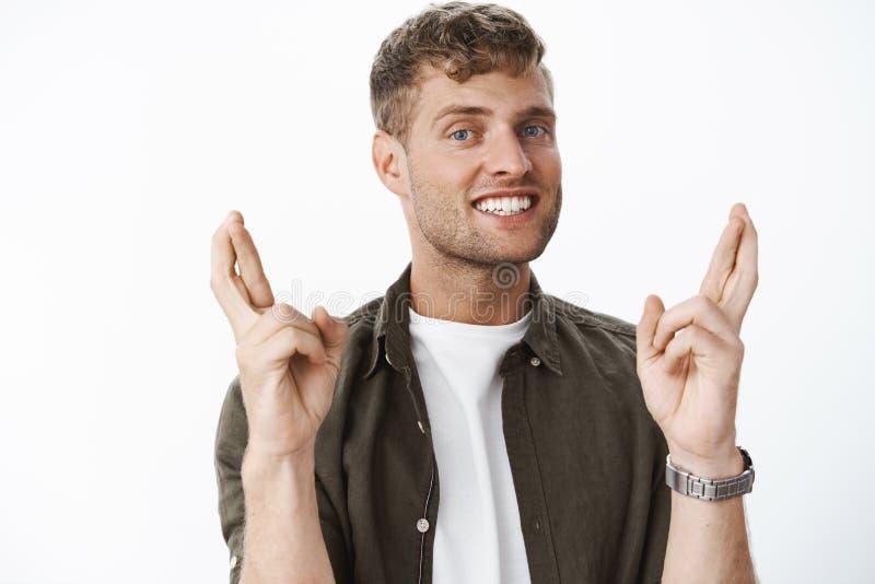 Το αισιόδοξο και αισιόδοξο όμορφο άτομο με τα διαγώνια δάχτυλα ξανθών μαλλιών για την καλή τύχη που προσεύχεται και που κάνει την στοκ εικόνες