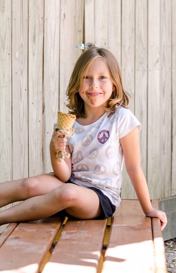 Το ακατάστατο μικρό κορίτσι χαμογελά δεδομένου ότι απολαμβάνει το παγωτό στοκ φωτογραφία με δικαίωμα ελεύθερης χρήσης