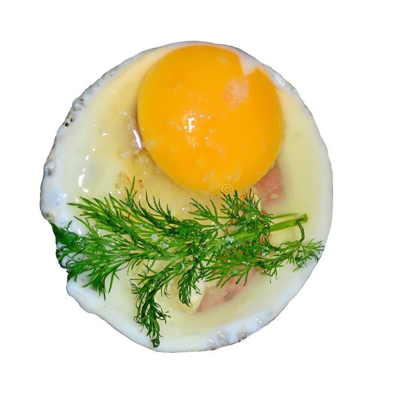 Το ακατέργαστο αυγό είναι τηγανισμένο σε ένα τηγανίζοντας τηγάνι, είναι έπειτα ένα κλαδάκι του άνηθου, μια φωτογραφία σε ένα άσπρ στοκ φωτογραφίες