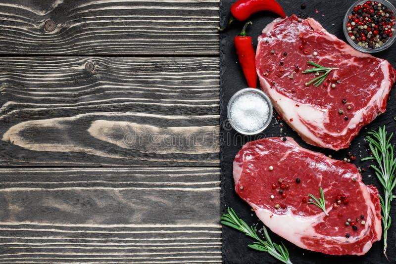 Το ακατέργαστο κρέας, η μπριζόλα βόειου κρέατος με τα καρυκεύματα και το δεντρολίβανο στη μαύρη πλάκα επιβιβάζονται στοκ εικόνες
