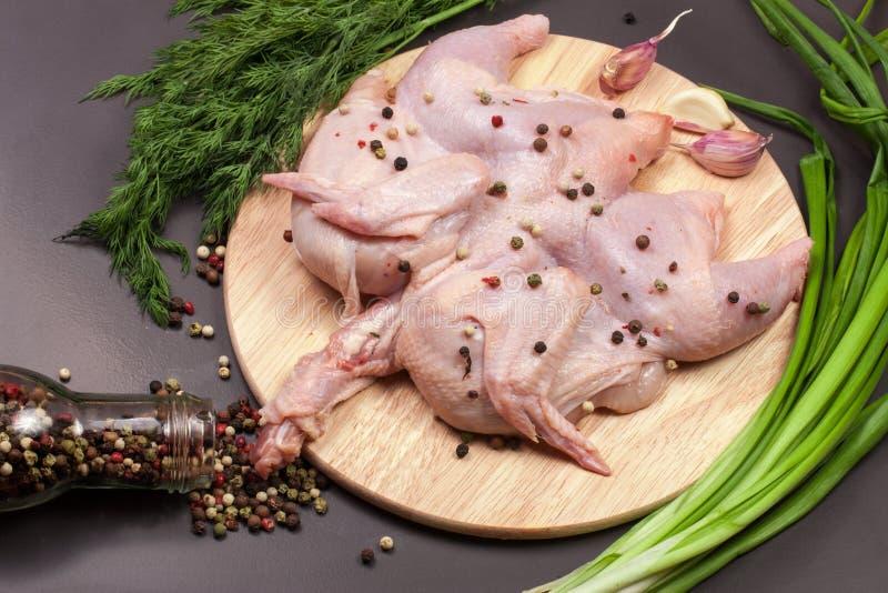 Το ακατέργαστο σφάγιο κοτόπουλου με peppercorns και η πρασινάδα στην κοπή επιβιβάζονται σε ένα σκοτεινό υπόβαθρο στοκ εικόνα με δικαίωμα ελεύθερης χρήσης