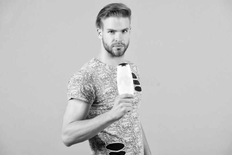 Το ακριβές πρόσωπο ατόμων κρατά το μπουκάλι σαμπουάν, γκρίζο υπόβαθρο Το άτομο απολαμβάνει τη φρεσκάδα μετά από να πλύνει την τρί στοκ εικόνες με δικαίωμα ελεύθερης χρήσης