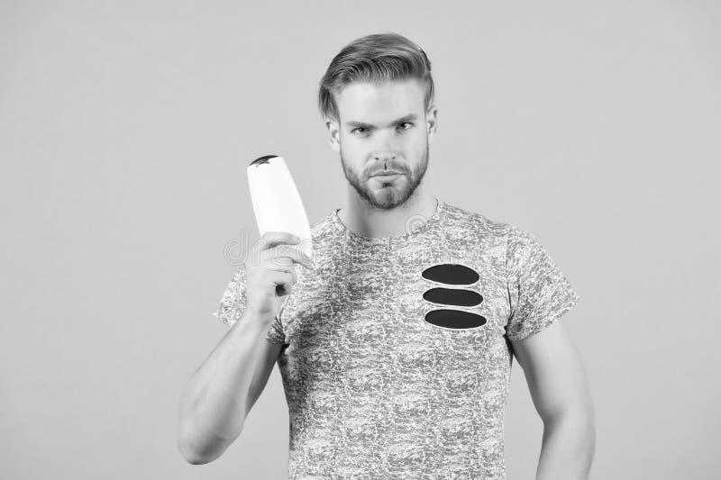 Το ακριβές πρόσωπο ατόμων κρατά το μπουκάλι σαμπουάν, γκρίζο υπόβαθρο Το άτομο απολαμβάνει τη φρεσκάδα μετά από να πλύνει την τρί στοκ εικόνα με δικαίωμα ελεύθερης χρήσης