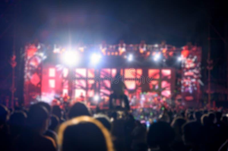 Το ακροατήριο νεολαίας σκιαγραφιών προσέχει τη συναυλία νύχτας του φωτός σκηνών στοκ φωτογραφία