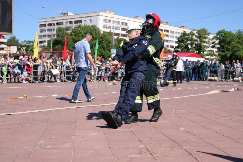 Το αλεξίπυρα κοστούμι και το κράνος πυροσβεστών ατόμων διασώζουν τον κίνδυνο στις ασκήσεις, στους ανταγωνισμούς πυρόσβεσης, Μινσκ στοκ φωτογραφία