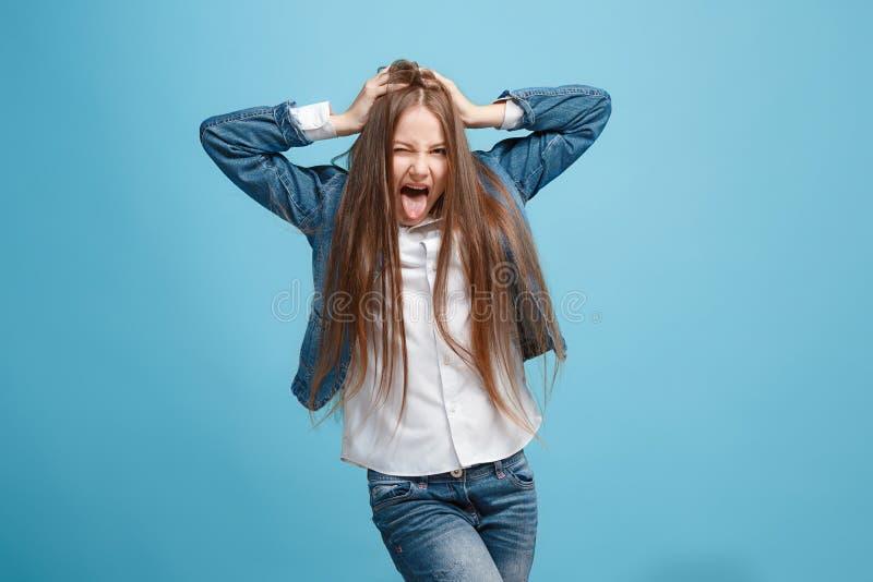 Το αλλήθωρο κορίτσι εφήβων την παράξενη έκφραση που απομονώνεται με στο μπλε στοκ φωτογραφίες