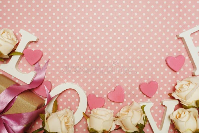 Το αλφάβητο λέξης αγάπης και το κιβώτιο δώρων με την ανθοδέσμη τριαντάφυλλων με το διαστημικό αντίγραφο στη ρόδινη Πόλκα διαστίζο στοκ εικόνες