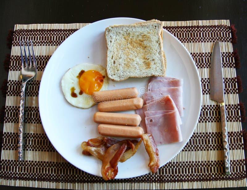 Το αμερικανικό πρόγευμα έχει το αναγνωριστικό σήμα λουκάνικων αυγών ζαμπόν στο tablemat στοκ φωτογραφία