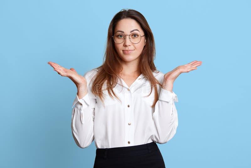 Το ανίσχυρο χαρισματικό νέο θηλυκό με τη μακρυμάλλη κάνοντας χειρονομία, που αυξάνει τα χέρια της, φαίνεται ταραγμένο για την εργ στοκ εικόνες