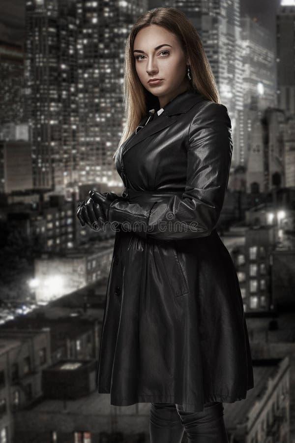 Το αναδρομικό πορτρέτο της απρόσιτης όμορφης γυναίκας στο μαύρο επενδύτη στέκεται στα πλαίσια της πόλης νύχτας Ταινία noir στοκ φωτογραφίες