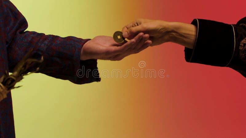 Το ανατολικό χέρι ατόμων πληρώνει ένα νόμισμα χαλκού και παίρνει το ξηρό καρύκευμα φύλλων κυλημένο στο έγγραφο από το χέρι πωλητώ στοκ φωτογραφίες