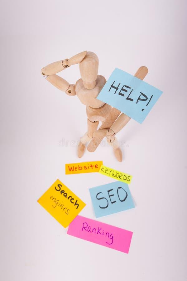 Το ανδρείκελο ένωσε την κούκλα κρατώντας τις κολλώδεις σημειώσεις SEO βοήθειας στύλων σημαδιών που ταξινομούν τον ιστοχώρο λέξεων στοκ φωτογραφία