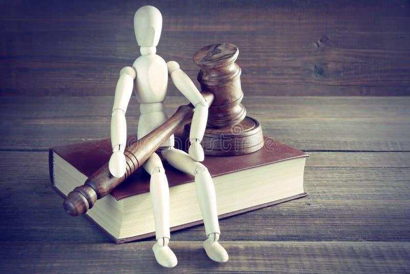 Το ανθρώπινο ειδώλιο με τους δικαστές ή Gavel Auctioneer κάθεται στο βιβλίο στοκ φωτογραφία με δικαίωμα ελεύθερης χρήσης