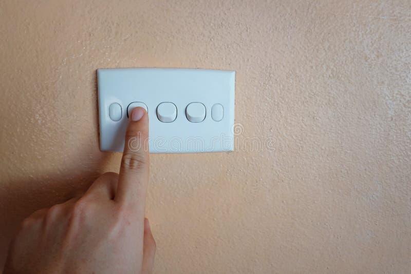 Το ανθρώπινο κουμπί ώθησης χεριών του λευκού ανάβει τον πορτοκαλή τοίχο στοκ φωτογραφίες με δικαίωμα ελεύθερης χρήσης