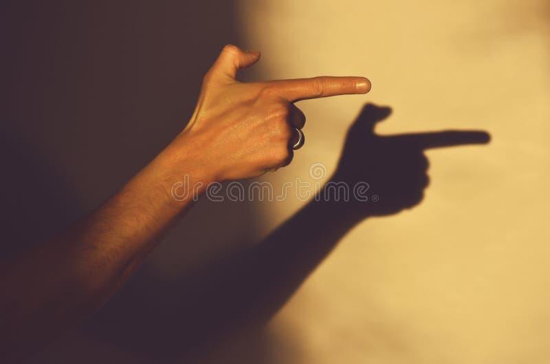Το ανθρώπινο χέρι δείχνει την κατεύθυνση που δείχνει με το αντίχειρα, σκιά στοκ εικόνα