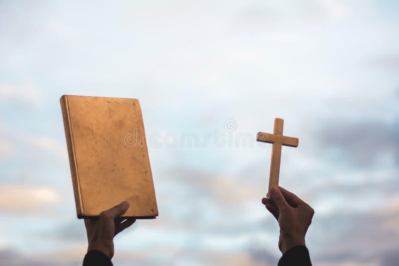 Το ανθρώπινο χέρι κρατά διαγώνιος και Βίβλος, στη λατρεία, στις αμαρτίες και στην προσευχή, Reli στοκ εικόνες