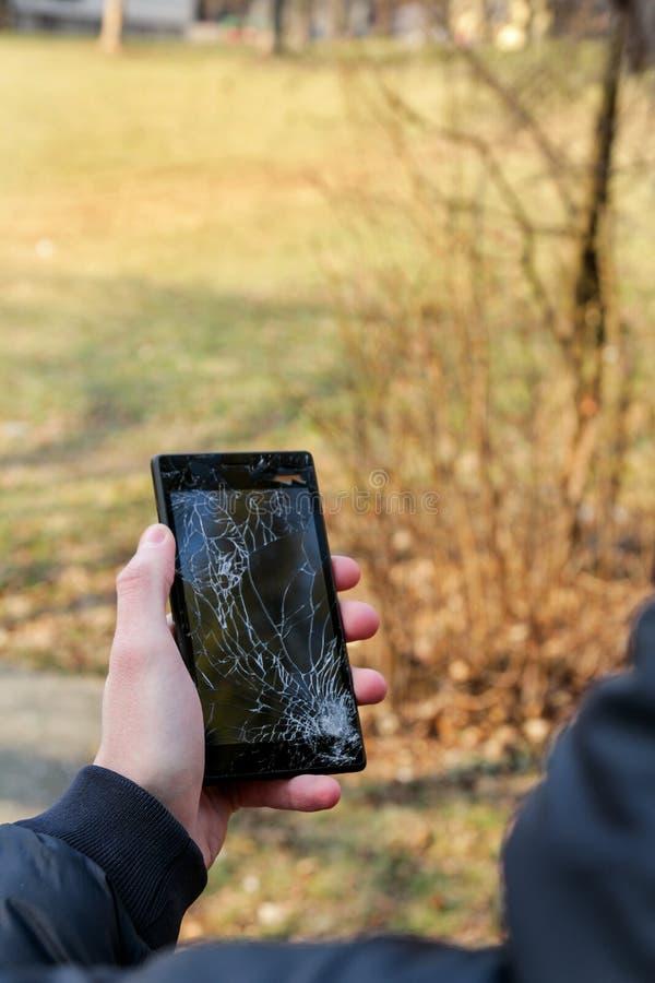 Το ανθρώπινο χέρι που κρατά το έξυπνο τηλέφωνο σπασμένο ράγισε τη χαλασμένη οθόνη στοκ εικόνα