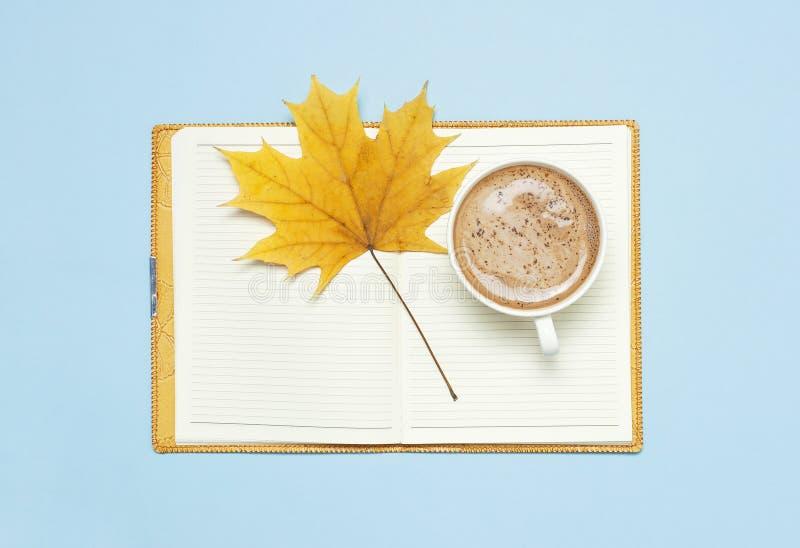 Το ανοιγμένος σημειωματάριο, το κακάο latte ή ο καφές στο φλυτζάνι, κίτρινο φύλλο σφενδάμου φθινοπώρου στο μπλε επίπεδο άποψης υπ στοκ εικόνες