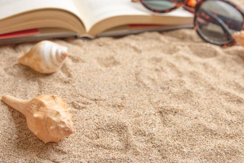 Το ανοικτό βιβλίο στην αμμώδη παραλία με τα κοχύλια και τα γυαλιά ηλίου θάλασσας, κλείνει επάνω την εικόνα τρόπου ζωής στοκ εικόνα