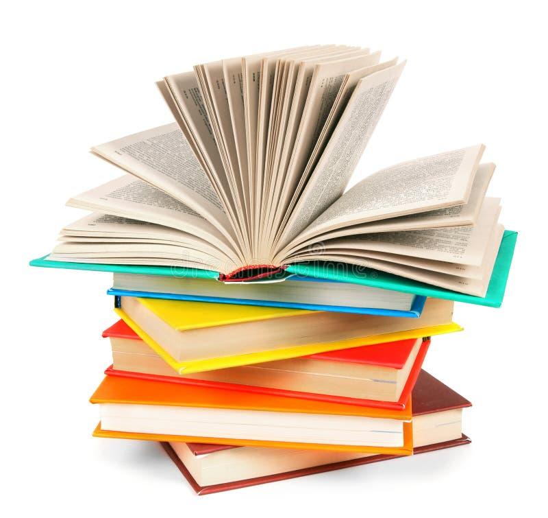 Το ανοικτό βιβλίο σε έναν σωρό των πολύχρωμων βιβλίων στοκ εικόνα με δικαίωμα ελεύθερης χρήσης