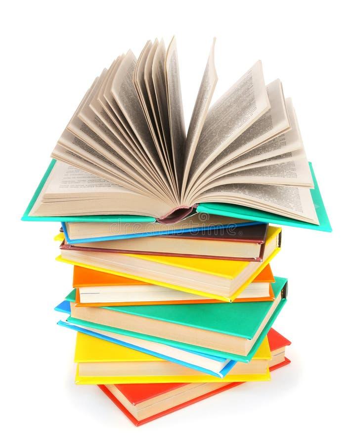 Το ανοικτό βιβλίο σε έναν σωρό των πολύχρωμων βιβλίων στοκ φωτογραφία