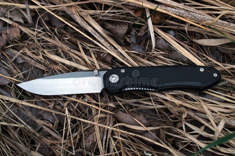 Το ανοικτό διπλώνοντας μαχαίρι με μια μαύρη λαβή βρίσκεται στη χλόη στοκ φωτογραφία με δικαίωμα ελεύθερης χρήσης