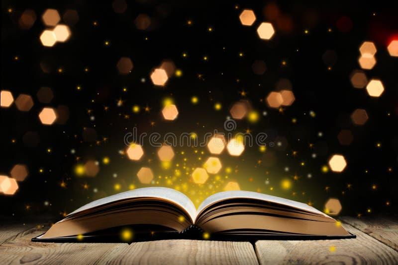Το ανοικτό μαγικό βιβλίο σε έναν ξύλινο πίνακα με ακτινοβολεί και bokeh φω'τα, και μαύρο υπόβαθρο με το διάστημα αντιγράφων για τ στοκ εικόνα με δικαίωμα ελεύθερης χρήσης