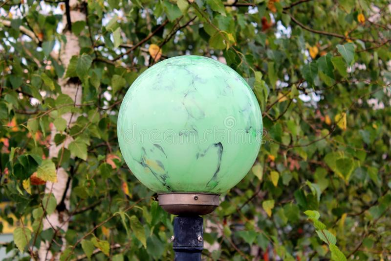 Το ανοικτό πράσινο μάρμαρο όπως τη σύσταση γύρω από το λαμπτήρα οδών τοποθέτησε στον πόλο μετάλλων στο φρέσκο πράσινο υπόβαθρο φύ στοκ εικόνες
