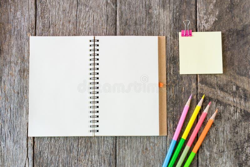 Το ανοικτό σημειωματάριο στο ξύλινο υπόβαθρο με τα χρωματισμένα μολύβια και φωνάζει στοκ φωτογραφία με δικαίωμα ελεύθερης χρήσης