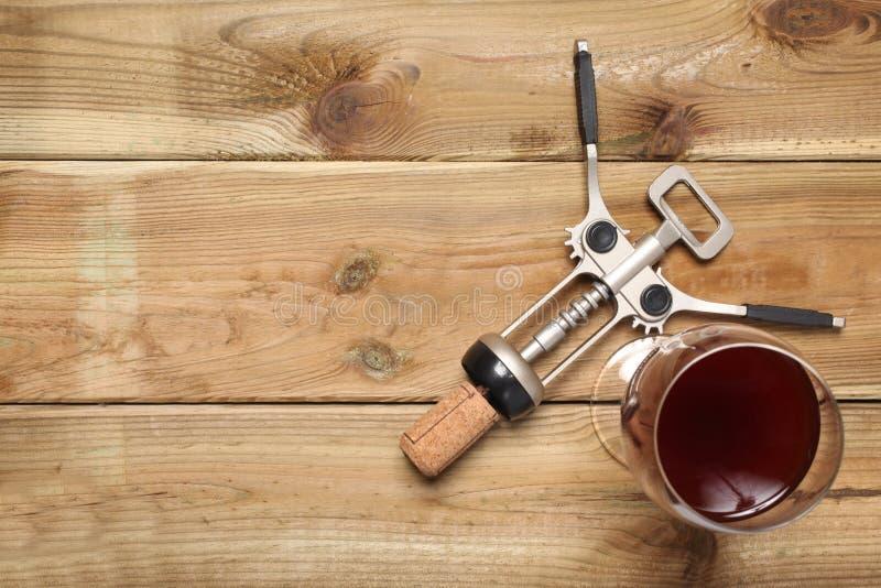 Το ανοιχτήρι και ένα ποτήρι του κόκκινου κρασιού στηρίζονται σε έναν αγροτικό ξύλινο πίνακα με το διάστημα αντιγράφων για το κείμ στοκ εικόνα με δικαίωμα ελεύθερης χρήσης